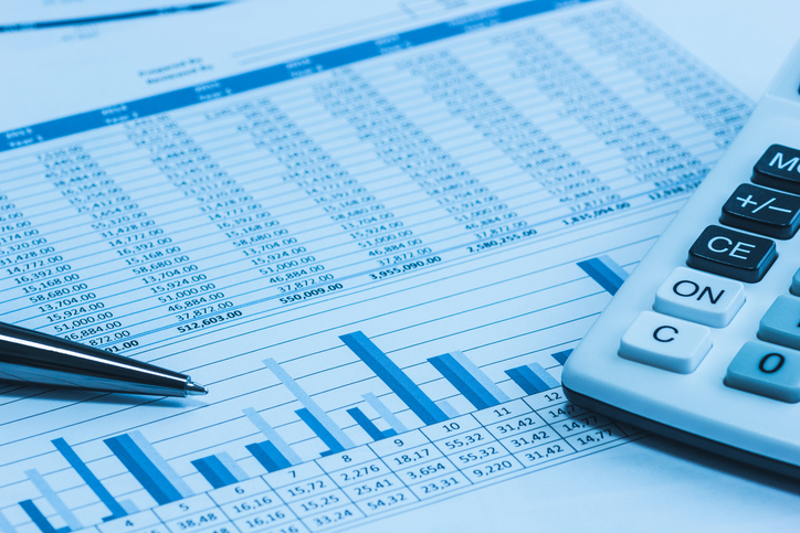 Accounting financial papers analysis charts with calculator, paper and pen in blue