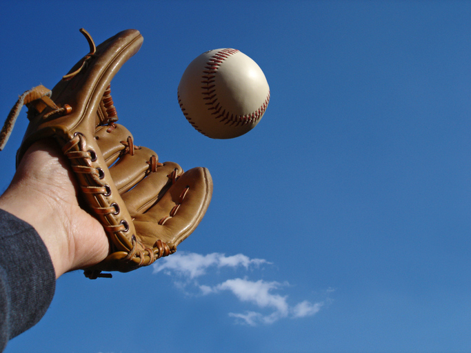 Catching a baseball against a blue sky. Right of photo offers negative space.